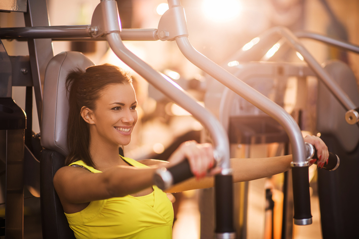 Young woman doing chest exercises on exercise machine at gym.