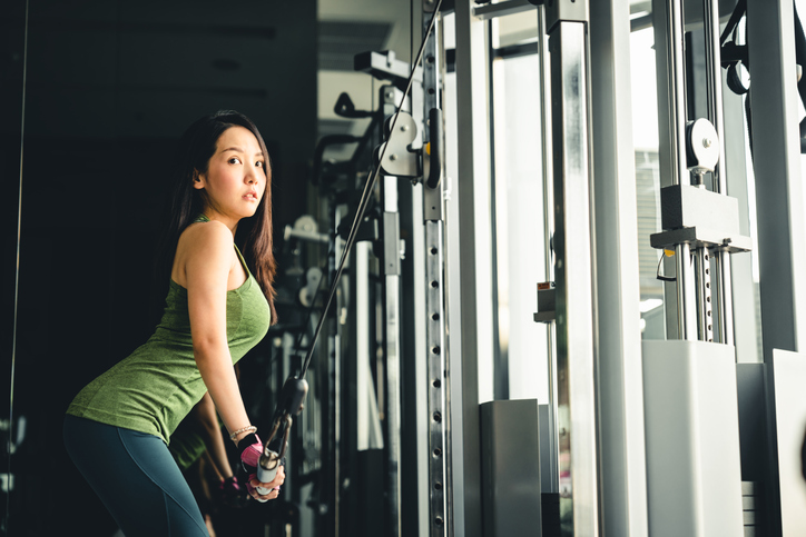 Sexy young Asian girl exercising at gym, training on pushdown cable machine, with copy space. Healthy lifestyle, sporty athletic woman, health club or fitness center advertisement concept