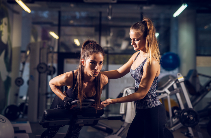 Portrait close up view of young smiling attractive healthy fitness sporty active slim girl doing low back exercise on the machine with weight while her pretty female personal trainer standing next to her and assisting in the gym.